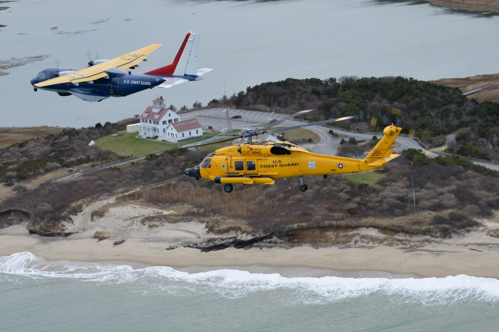 The centennial HC-144 Ocean Sentry airplane and MH-60 Jayhawk helicopter fly over a retired Coast Guard station museum at Coast Guard beach, Eastham, Massachusetts, Monday, Dec. 16, 2019. Coast Guard Air Station Cape Cod will celebrate 104 years of aviation in Mass., and 50 years on Cape Cod. (U.S. Coast Guard photo by Petty Officer 2nd Class Nicole J. Groll)