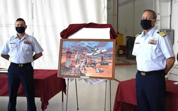 Command Master Chief Jacob Linder and Capt. Scott Langum, commanding officer, Air Station Cape Cod, stand next to a painting to commemorate the 50th anniversary of the air station. The groundbreaking ceremony took place August 29, 1970, and a few weeks later the first aircrafts were transferred from the base in Salem and Rhode Island. (U.S. Coast Guard photo by Petty Officer 2nd Class Amanda Wyrick)