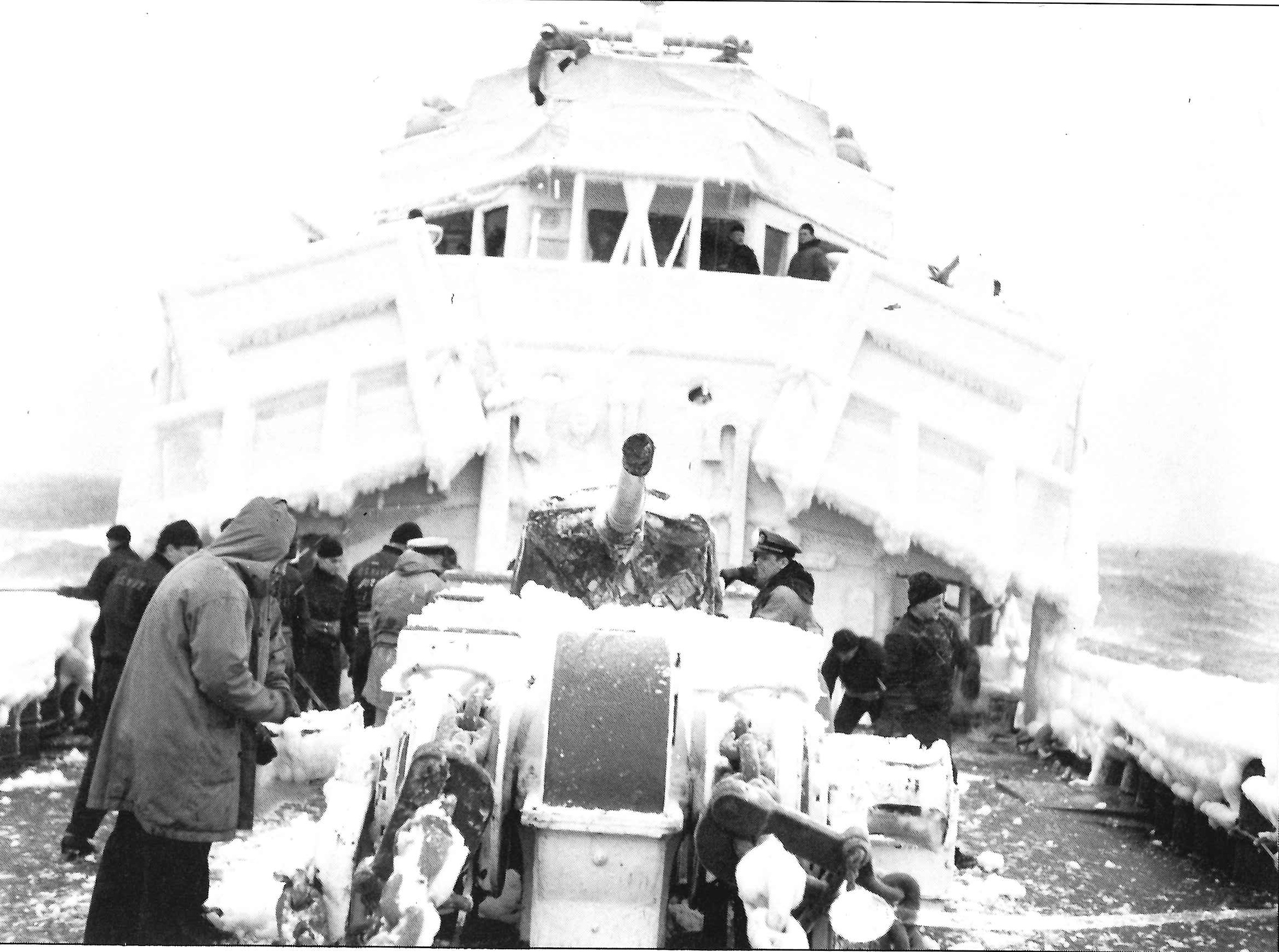 7. Northland's crew chipping ice. If allowed to accumulate the ice could make ships dangerously top-heavy. (U.S. Coast Guard)