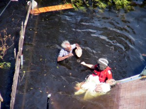 A Coast Guard rescue swimmer saving an elderly victim in 2005's Hurricane Katrina. (U.S. Coast Guard Collection)