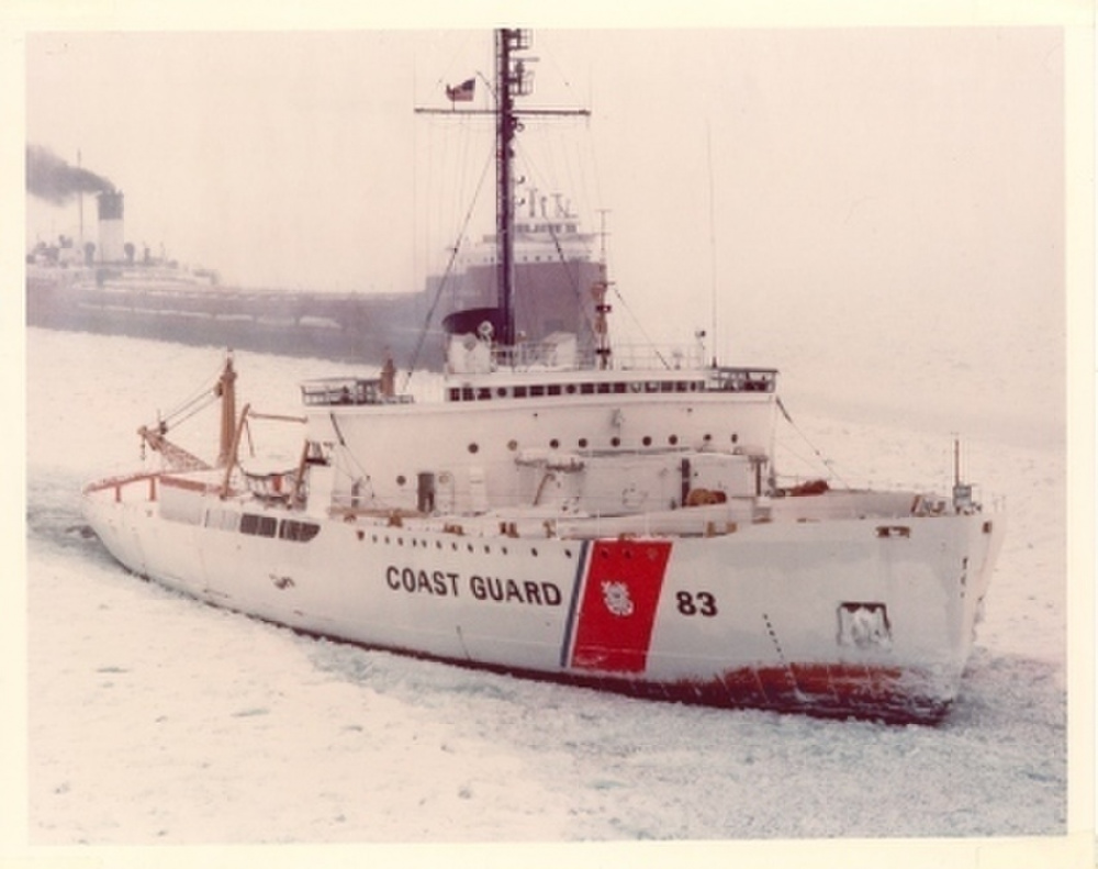 "Coast Guard Cutter Mackinaw sporting the new ""Racing Stripe"" on its white hull escorting a Great Lakes bulk carrier through the ice. (U.S. Coast Guard)"